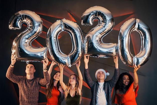 Группа красивых молодых людей празднуют новый год. Premium Фотографии