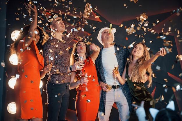 ポーズをとって雪だるまとシャンパンを楽しんでいる友人のグループ。新年のお祝い。 Premium写真