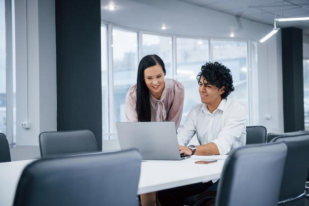コンピューターを一緒に見ています。ラップトップを使用して仕事をしているときに笑みを浮かべて近代的なオフィスで陽気な同僚 Premium写真