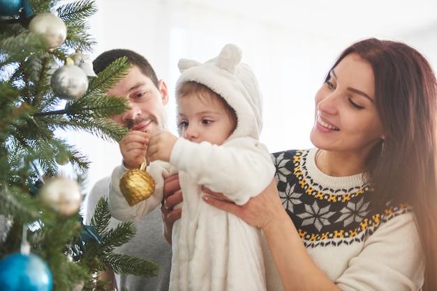 幸せな家族が一緒にクリスマスツリーを飾る。父、母と娘。かわいい子 Premium写真
