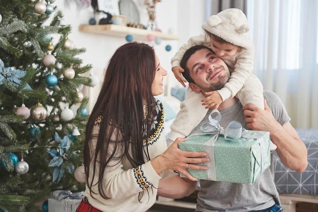 モミの木の近くで一緒に贈り物を開く朝のクリスマスに幸せな家族。家族の幸せと幸福の概念 Premium写真