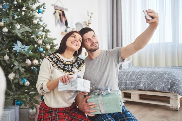 Семья собралась вокруг елки, используя планшет Premium Фотографии