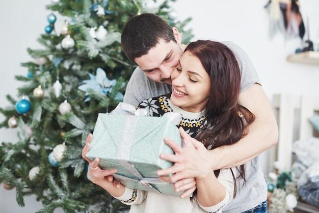 若いカップルがクリスマスを祝います。男が突然妻にプレゼントを贈った。 Premium写真