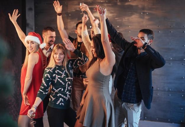 Вечеринка с друзьями. они любят рождество. группа веселых молодых людей, перевозящих бенгальские огни и шампанское флейты, танцы в новогодней вечеринке и выглядит счастливым. концепции об образе жизни единения Premium Фотографии