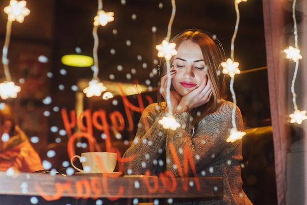 Молодая красивая женщина, сидя в кафе, пить кофе. модель слушает музыку. Premium Фотографии
