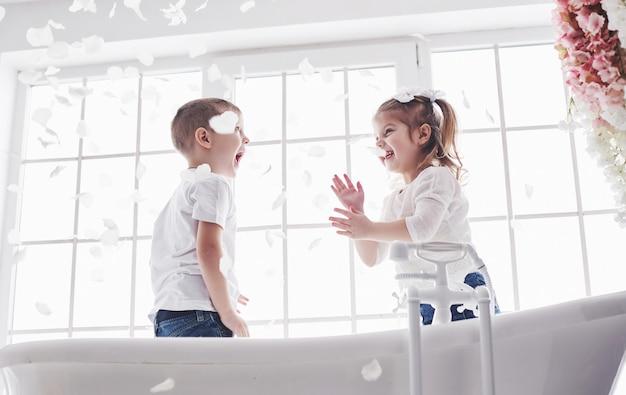 家庭の浴室でバラの花びらと遊ぶ子供。小さな女の子と男の子が一緒に楽しさと喜びを見せびらかす。幼少期と夢、幻想、想像力の実現 Premium写真