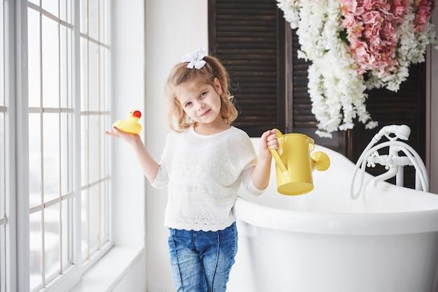 Смешная маленькая девочка с вьющимися волосами. будьте готовы принять ванну. просторная светлая ванная комната. здоровое и чистое тело. забота о себе с детства Premium Фотографии