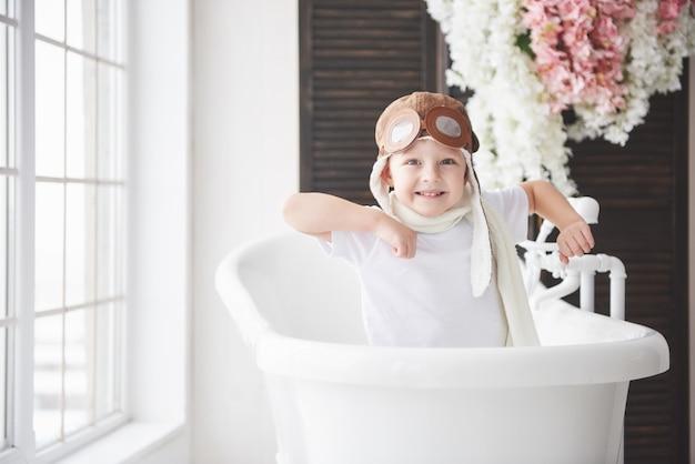 バスルームで遊んでパイロット帽子で幸せな子供。子供の頃。ファンタジー、想像力。 Premium写真