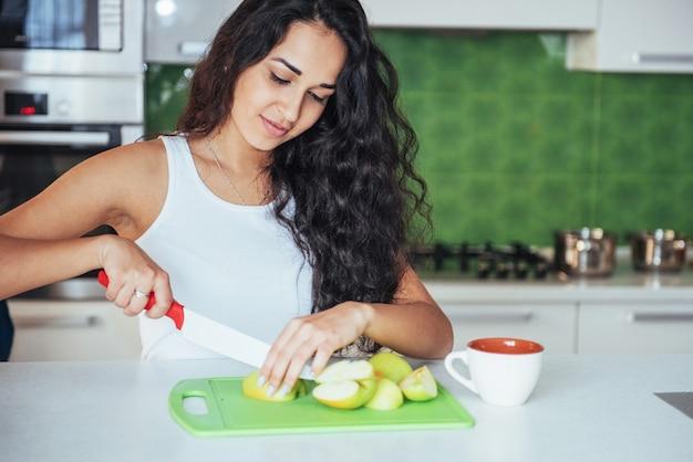 Женщина нарезать овощи вместе на кухне. Premium Фотографии
