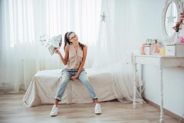 クローズアップかわいいブルネットの少女、広く笑って、透明と銀の風船で遊ぶ。彼女は眼鏡とねじれた髪を着ています。 Premium写真