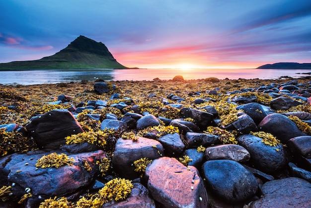 風景と滝の美しい夕日。アイスランドのカーキュフェル山 Premium写真