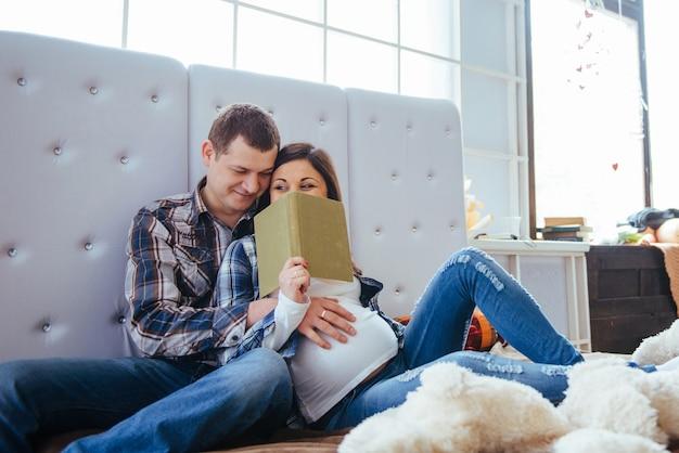 Беременная женщина с мужем в постели Premium Фотографии