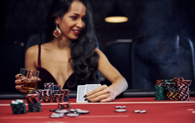Женщина в элегантной одежде сидит в кассино за столом и играет в покер Premium Фотографии