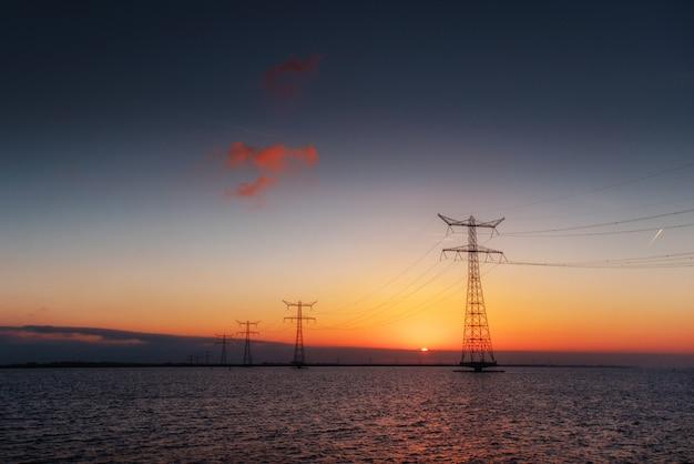 幻想的な日没時の水の上の電線 Premium写真