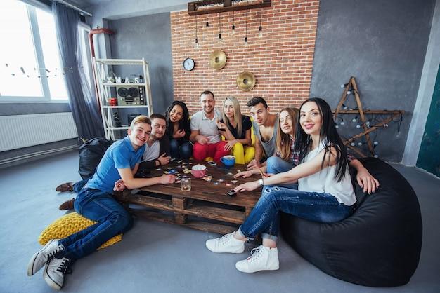 木製のテーブルに座っている創造的な友人のグループ。ボードゲームをプレイしながら楽しんでいる人 Premium写真