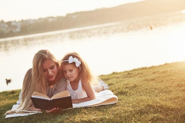 Мать с ребенком читает книгу на траве Premium Фотографии