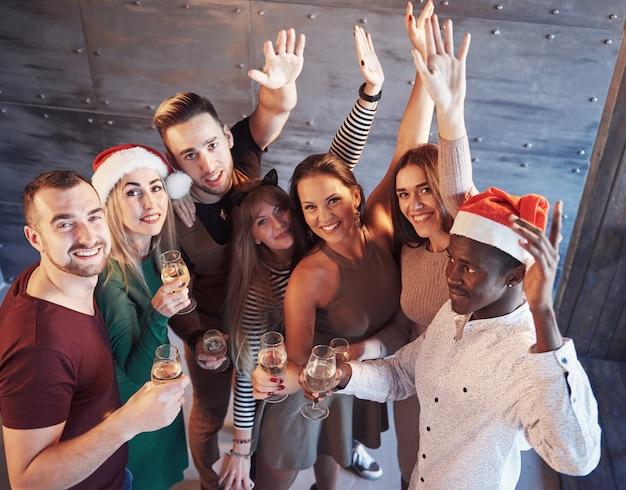 新年が来ています!感情的なライフスタイルの人々の概念をポーズ、パーティーのサンタ帽子で陽気な若い民族の人々のグループ Premium写真