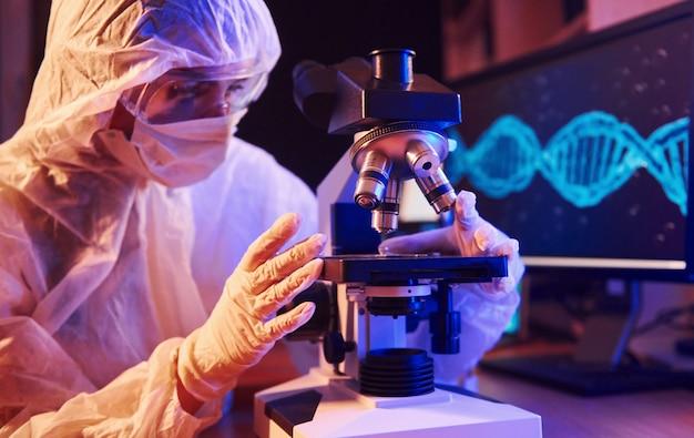 コンピューター、顕微鏡、コロナウイルスワクチンを検索する医療機器を備えたネオン照明の実験室に座っているマスクと白い制服を着た看護師 Premium写真