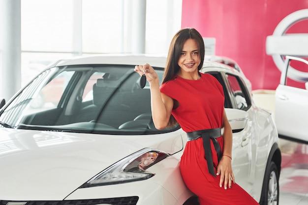 新しい車のキー、ディーラー、販売コンセプトを引き渡す車のセールスマンの笑顔。 Premium写真