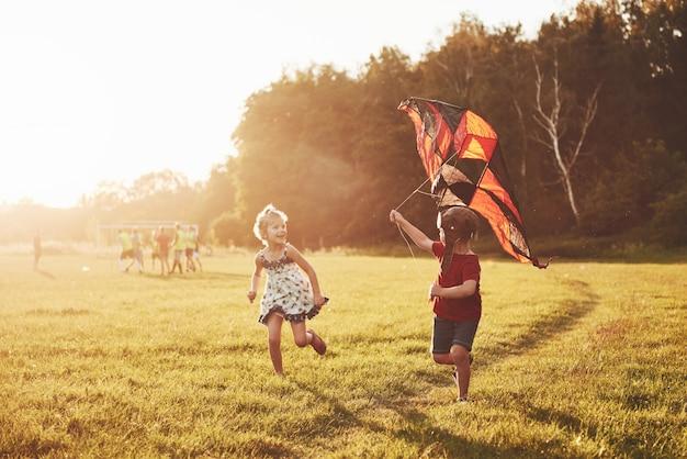 Счастливые дети запускают змея в поле на закате. маленький мальчик и девочка на летних каникулах Premium Фотографии