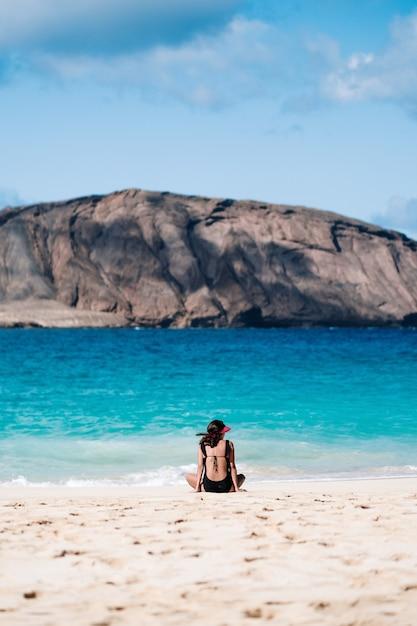 海を見ながらビーチに座っている女の子 Premium写真
