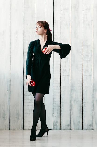 赤いカスタネットと黒のドレスで若いかなり踊っている女の子 Premium写真
