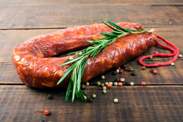 Деликатесная копченая колбаса (салями) на деревянной доске Premium Фотографии