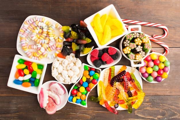 Различные красочные конфеты на белом блюде за деревянным столом Premium Фотографии