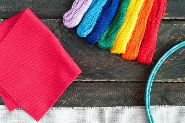 刺繍用アクセサリー。キャンバス、木製の背景に刺繍と糸のフロスのフープ Premium写真