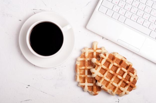 ノートパソコン、コーヒーカップ、明るい背景にワッフルデスクテーブル Premium写真