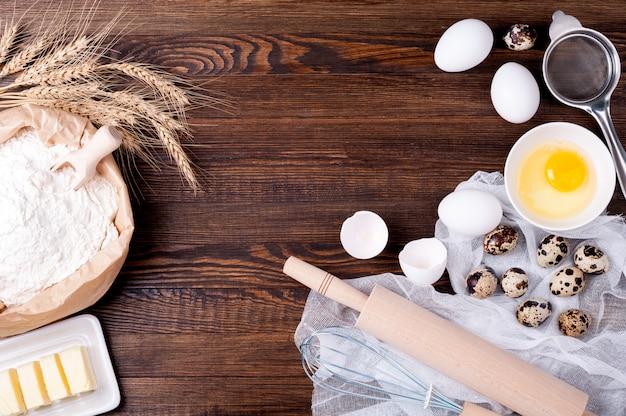 Мука в бумажном пакете, яйца, масло, скалка и венчик для выпечки Premium Фотографии