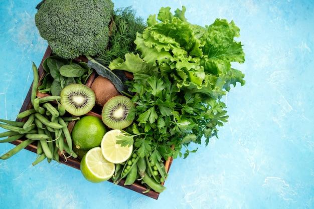 ブロッコリー、ほうれん草、キウイ、レタス、パセリ、ディル、アスパラガスの豆、青の背景にライム Premium写真