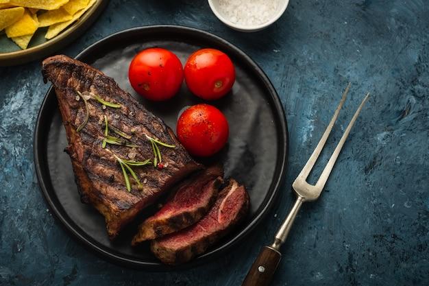 おいしいビーフステーキ、サラダ、ハーブ、チェリートマト Premium写真