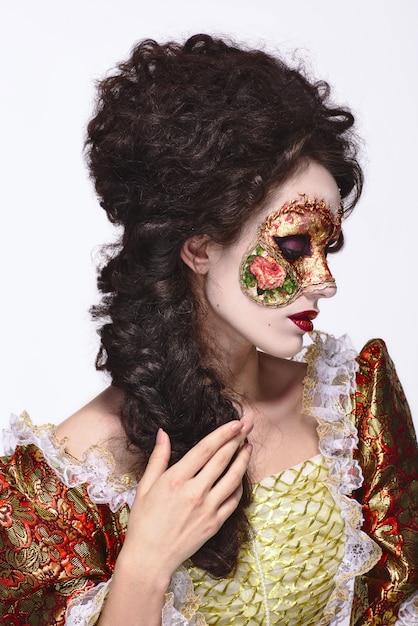 ベネチアンマスク。ヴィンテージのドレスと彼の顔にマスクで美しい女性。 Premium写真