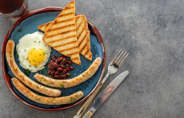 グレーの目玉焼き、ソーセージ、豆を使った伝統的なフルイングリッシュブレックファースト。上面図 Premium写真