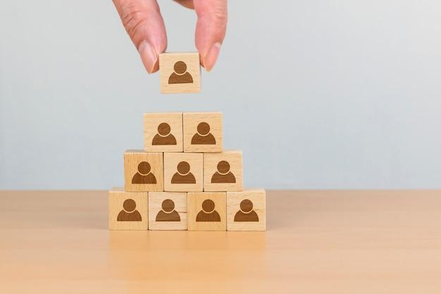 Бизнес-концепция управления персоналом и найма, рука положить деревянный куб на верхней пирамиде, копия пространство Premium Фотографии