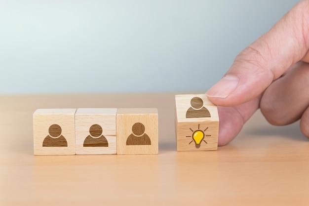 Концепция творческой идеи и инноваций. рука перевернуть деревянный куб с головой человека символ и значок лампочки Premium Фотографии