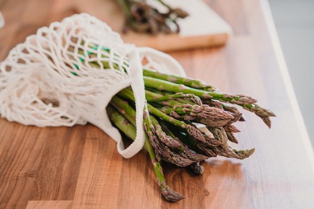 木製の背景にロープバッグで新鮮な有機グリーンアスパラガス Premium写真
