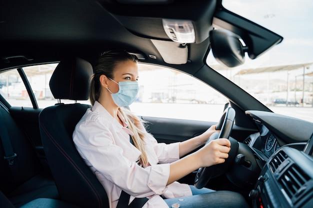 Женщина с маской за рулем автомобиля во время пандемии коронавируса Premium Фотографии