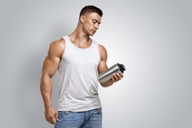 Мускулистый фитнес мужчина держит протеиновый коктейль Premium Фотографии