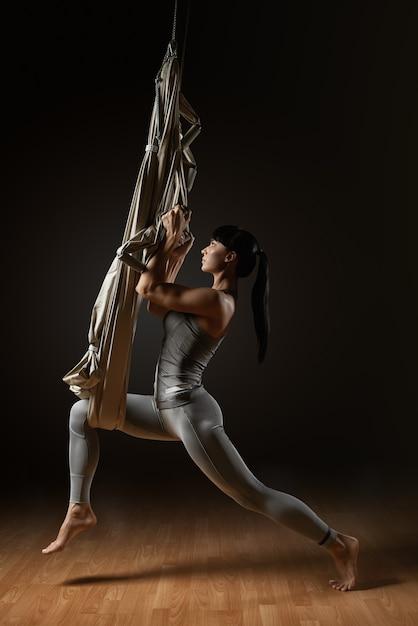 Девушка практикует воздушную йогу растяжения Premium Фотографии