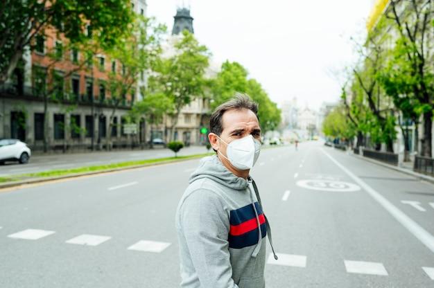 Человек идет по городу мадрид с маской Premium Фотографии