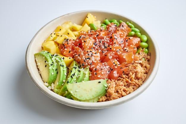 Выложить салат из лосося, авокадо, манго, эдамама, хрустящего лука и семян кунжута. Premium Фотографии