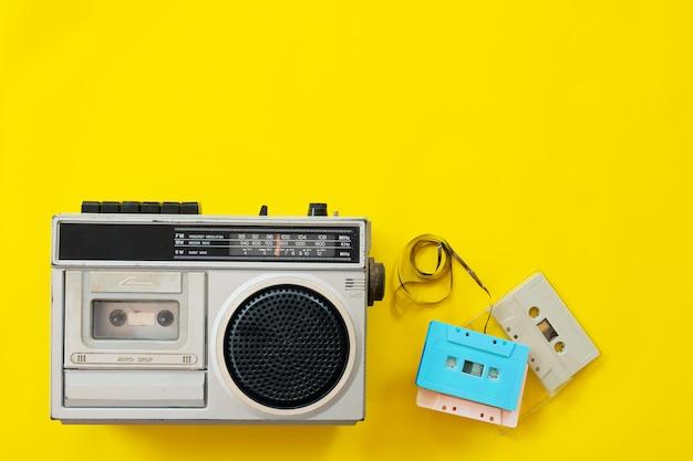 黄色の背景にヴィンテージラジオとカセットプレーヤー Premium写真