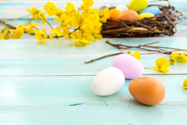 素朴な木製の板の背景に花と巣でカラフルなイースターエッグ Premium写真