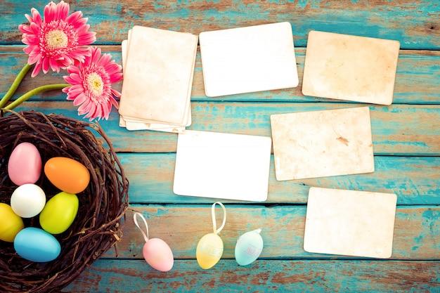 カラフルなイースターエッグの花と木のテーブルに空の古い紙の写真アルバムの巣 Premium写真