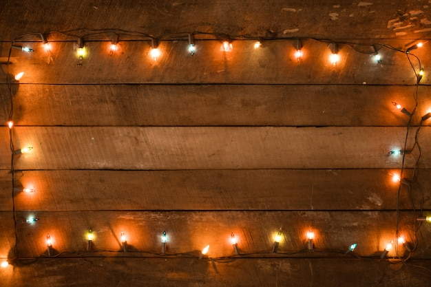 Рождественские огни украшения лампы на старой деревянной доске Premium Фотографии