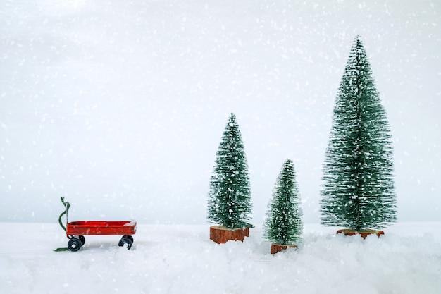 Винтажная открытка с рождеством миниатюрная елка в снежном зимнем лесу. Premium Фотографии