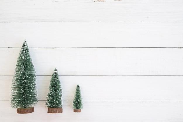 Рождественская миниатюрная елка, рождественские украшения и орнамент на белом фоне древесины. винтажный стиль. вид сверху. Premium Фотографии