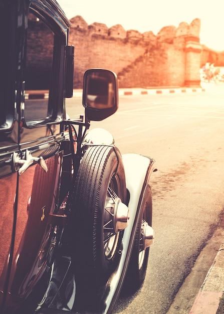 Старый классический автомобиль, припаркованный на улице в урбанистическом стиле Premium Фотографии